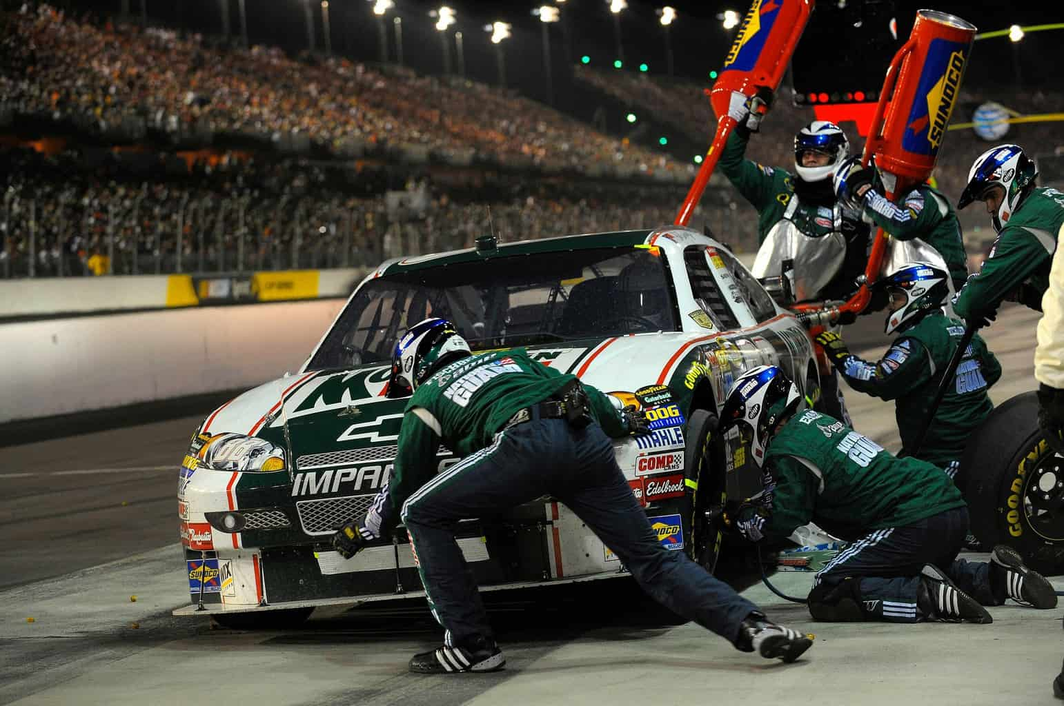 Nascar pitstop mechanic is seen using an impact wrench