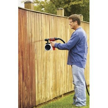 Man using an HVLP paint sprayer on a fence